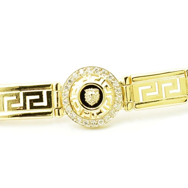 Złota bransoleta z drogą grecką i głową lwa.