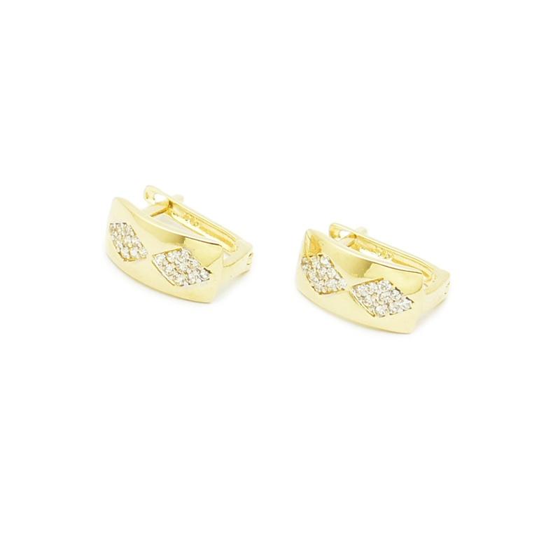 Białe cyrkonie oprawione w złotych kolczykach.
